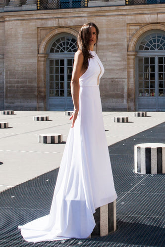 Model in Paris, full length, standing on platform wearing low back wedding dress.