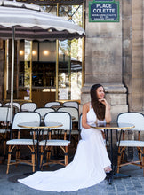 Load image into Gallery viewer, Bride in Paris sitting outside at cafe wearing halter neck wedding dress.