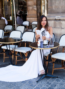 Model in cafe in Paris reading book, wearing backless boho wedding dress.