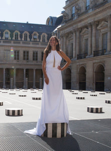 Bride posing on art in Paris, facing us, in open back halter top bridal gown.