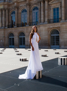 Model standing on platform, in fitted high neck wedding dress in Paris.