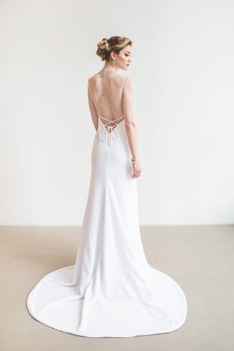 Model, full length from behind, wearing V-neck lace up backless crepe wedding dress.