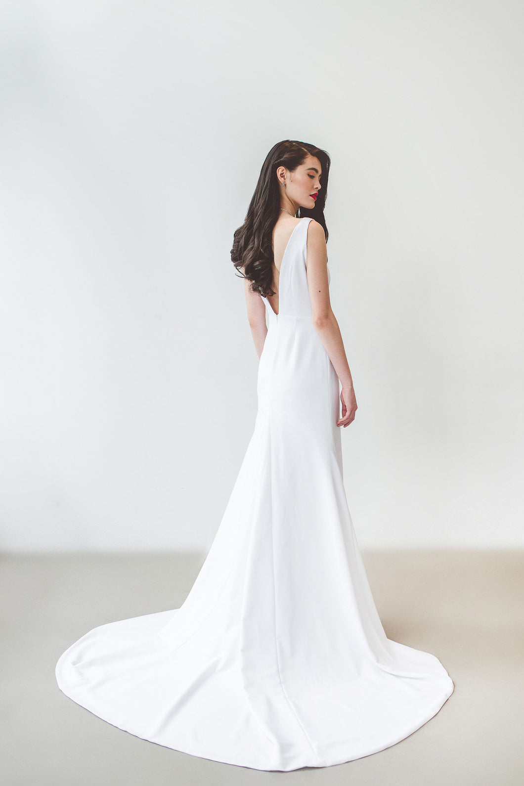 A unique backless minimalist wedding dress with long train handmade in Vancouver.