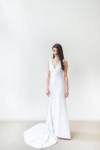 A minimalist chic sleeveless wedding dress with fit and flare skirt for the modern boho bride.