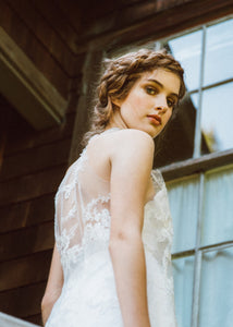 Model looking back at camera, showing back detail of sleeveless lace wedding dress.