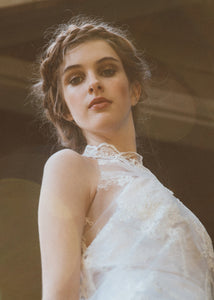 Detail shot of model wearing high neck sleeveless short lace wedding dress.