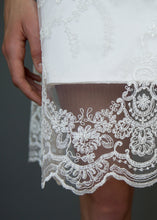 Load image into Gallery viewer, Fabric close up of hemline overlay on short skirt on lace wedding dress for Vancouver brides.
