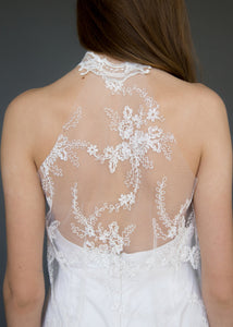 Detail shot of back of model wearing lace overlay dress over short strapless wedding dress.