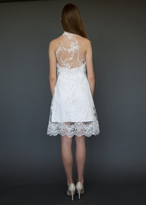 Model facing away, wearing low back with lace short wedding dress.