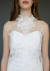 Close up of torso of strapless wedding dress with high neck lace overlay in a short version.