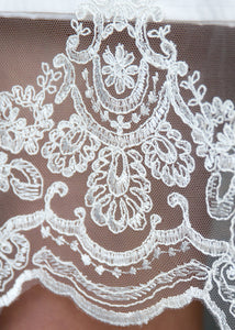 Detail of lace hem of short modern wedding dress from Vancouver wedding dress shops.