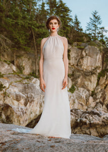 Bride standing on rock wearing backless halter sheath wedding dress by Vancouver bridal designer.