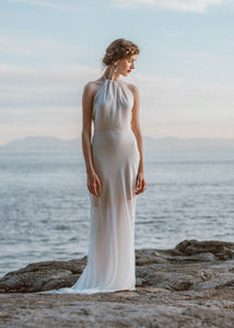 Bride standing on rock looking away wearing high neck flowy bridal gown.