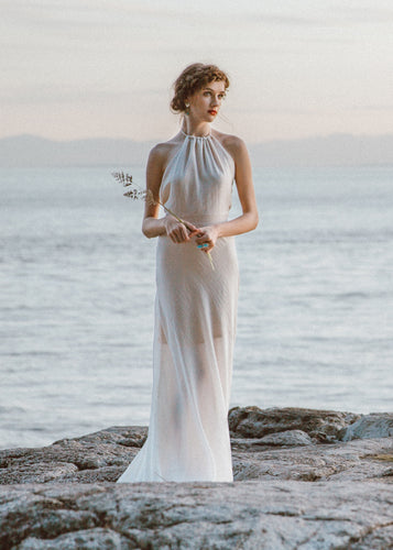 Bride standing on rock wearing halter wedding dress.