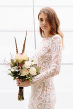 Load image into Gallery viewer, Bride with flowers wearing long sleeve lace wedding dress in Vancouver.