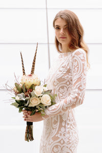Bride with flowers wearing long sleeve lace wedding dress in Vancouver.