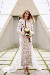 Bride posing with flowers wearing high neck lace wedding gown in Vancouver.