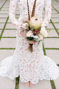 Long sleeve lace worn by bride, in a body shot holding flowers, showcasing long sleeve lace gown.
