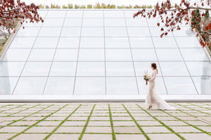 Bride walking, far back, against glass structure in Vancouver in wedding dress.