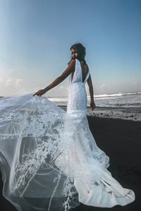 Vancouver bride holding up white lace wedding dress on beach.
