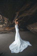 Load image into Gallery viewer, Bride in cave with arms up wearing a boho fit-and-flare lace wedding dress.