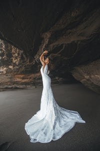 Bride in cave with arms up wearing a boho fit-and-flare lace wedding dress.