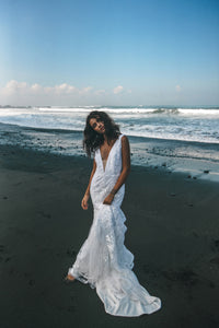 Bride posing on beach with sleeveless wedding dress in lace with trumpet skirt.