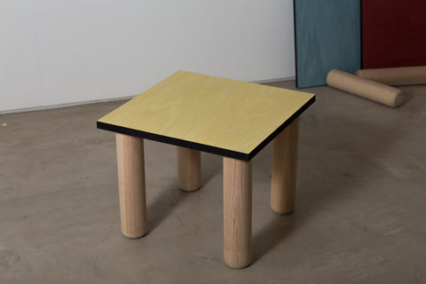 A yellow coloured veneered side table