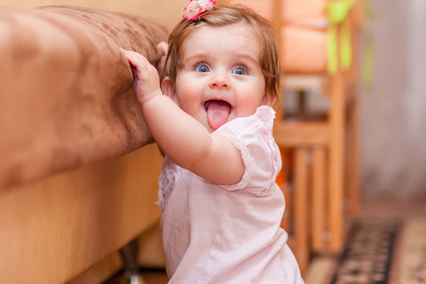 Baby play at home - learning to walk holding on to sofa