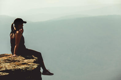 Woman sitting on edge of a cliff