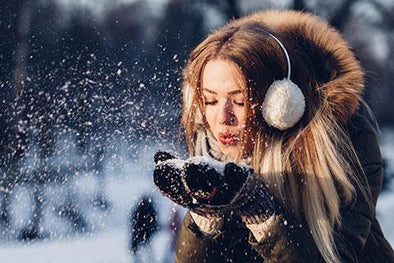 Lady blowing snow out of her hand