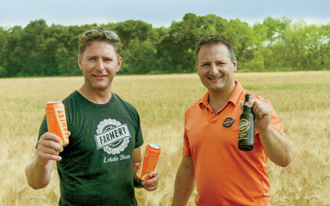 Chris and Lawrence showcasing the premium Lager beer standing in the farm field