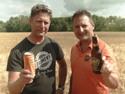 Chris and Lawrence on the farm holding the premium lager can and bottle