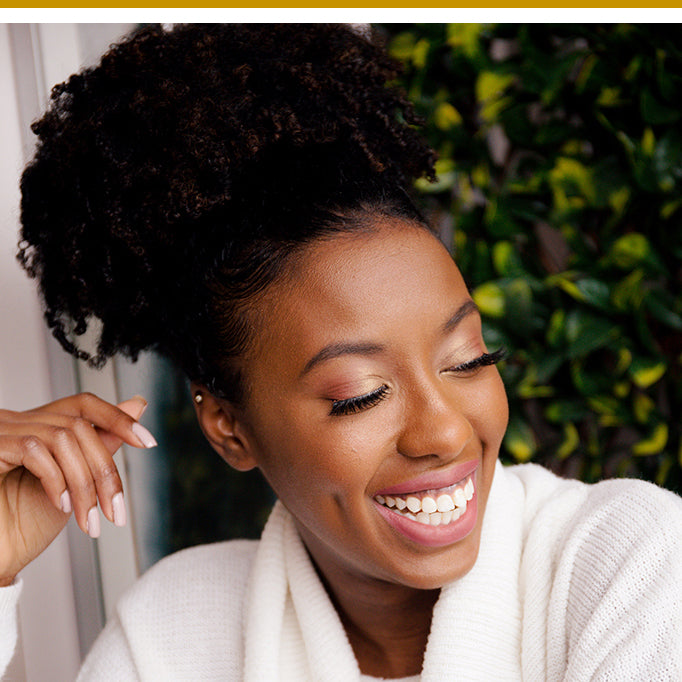 Woman laughing with beautiful natural curly hair styled in an updo