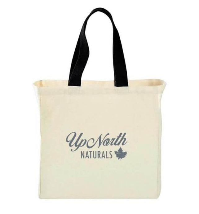 Image of cream tote back with black handle with a blue up north naturals logo on the front