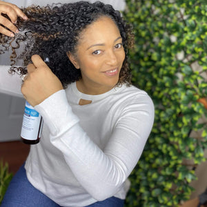 Women with naturally curly hair sectioning her hair and spraying freshen up hair mist