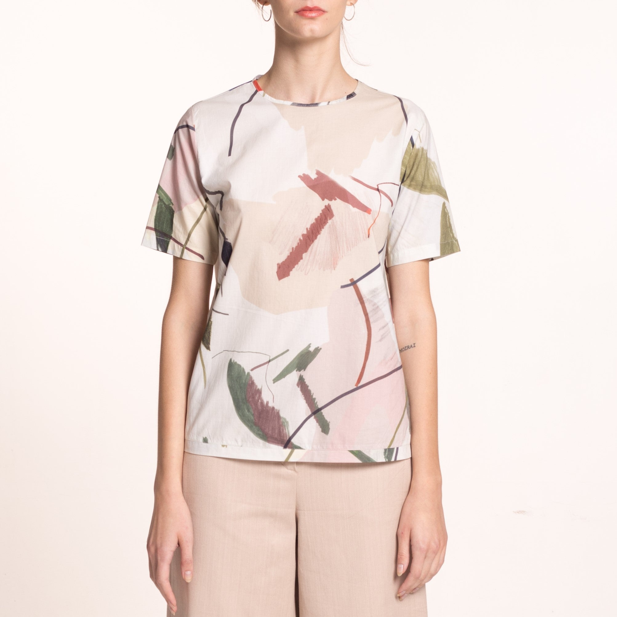 The model wears a sustainable, organic cotton, short sleeved blouse with round neckline and printed beige fabric with coloful shapes, close up.