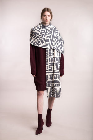 The model wears a grey and cream, sustainable organic cotton, knitted arty bricks scarf.
