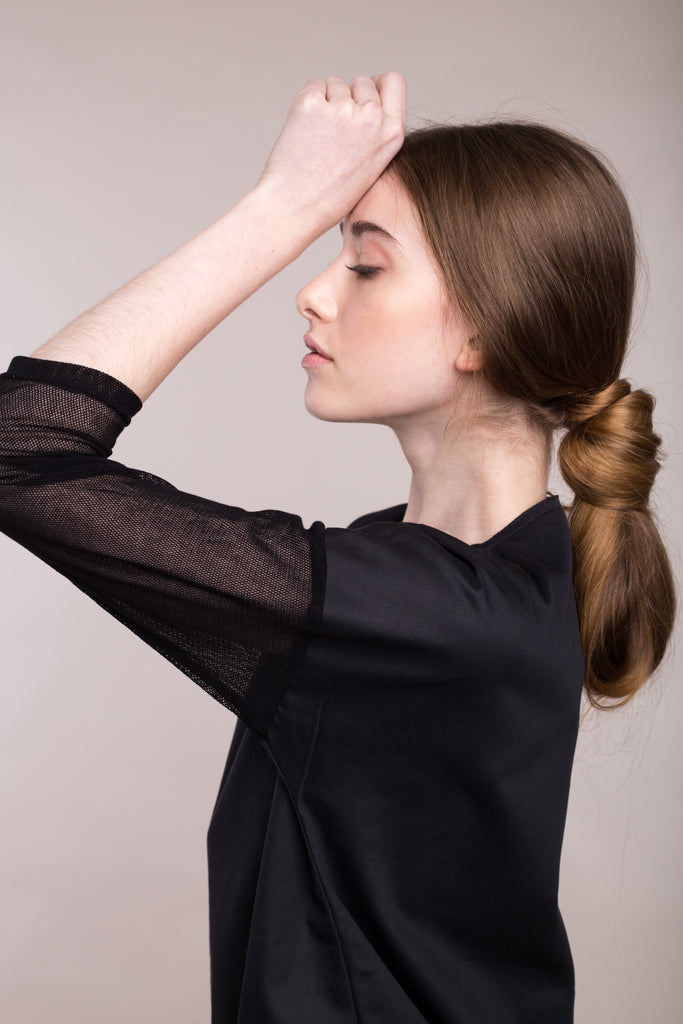 The model wears a black, sustainable organic cotton, tulle-sleeve dress, close up.