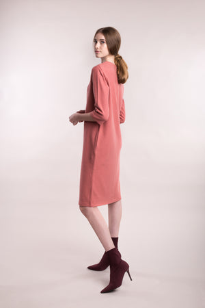The model wears a peach, sustainable organic cotton, soft corduroy cocktail dress, back view.