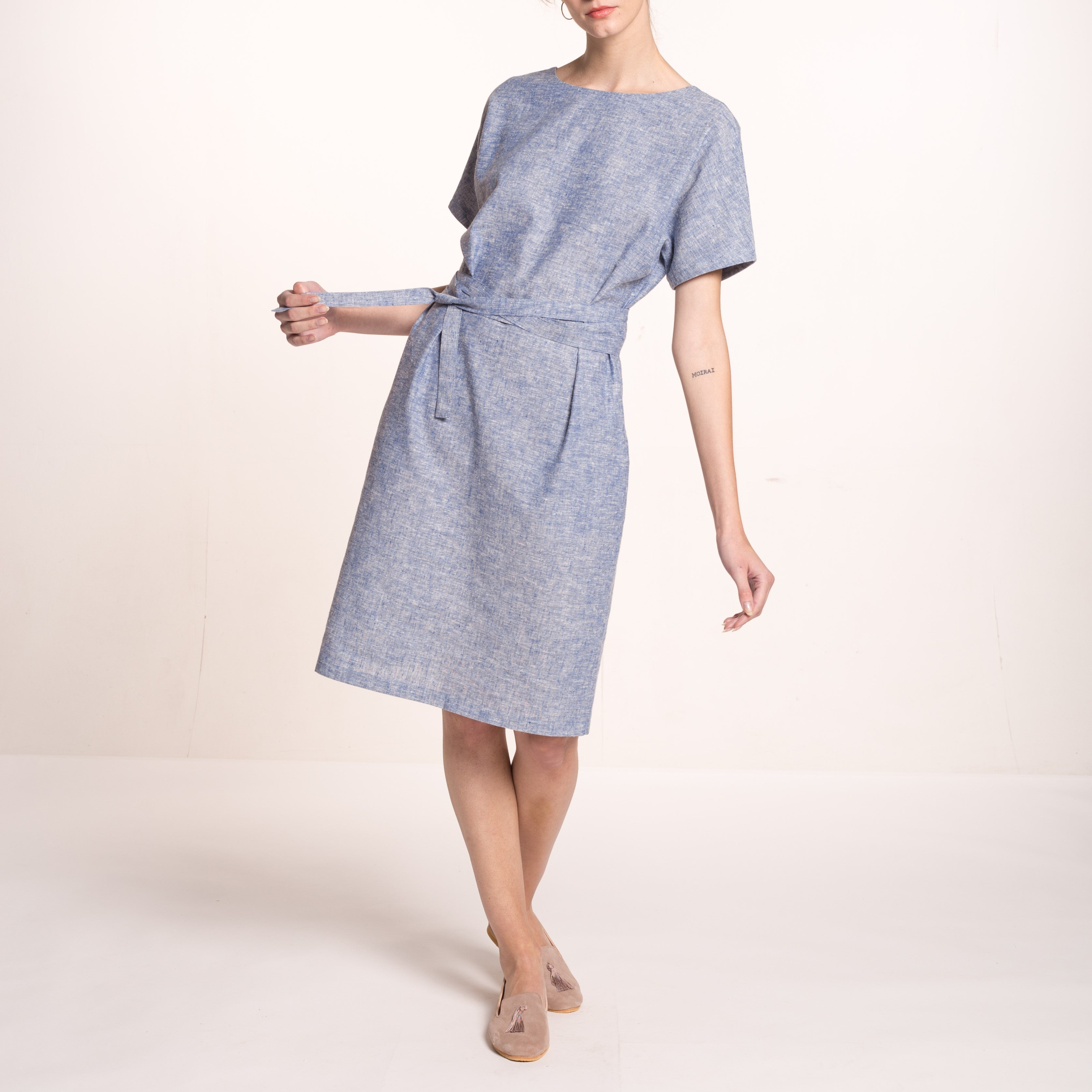 The model wears a light blue, sustainable, organic cotton and hemp dress, with short sleeves and round neckline and a fabric belt, close up.
