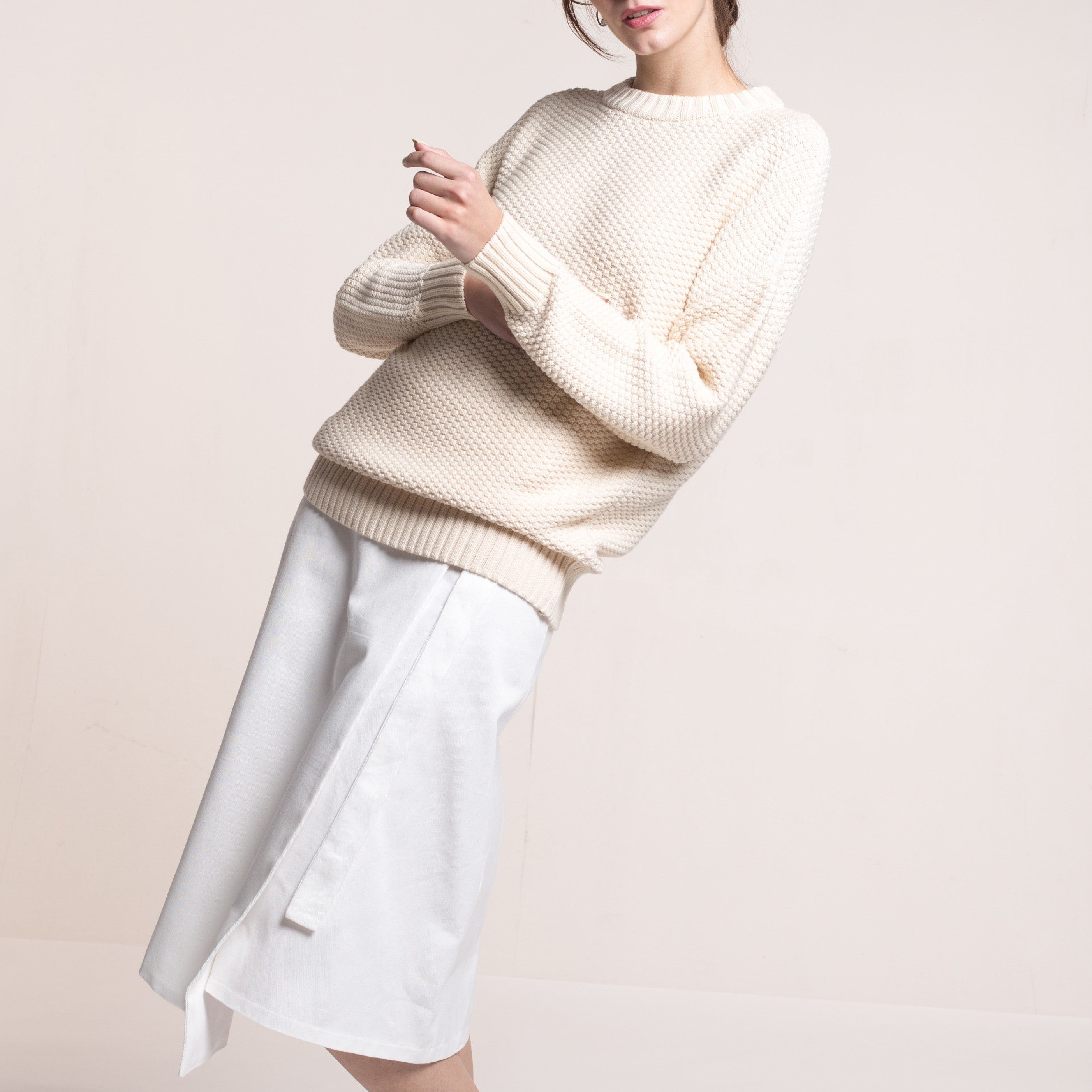 The model wears a natural sustainable organic cotton knitted rice cubes pullover and a white skirt.