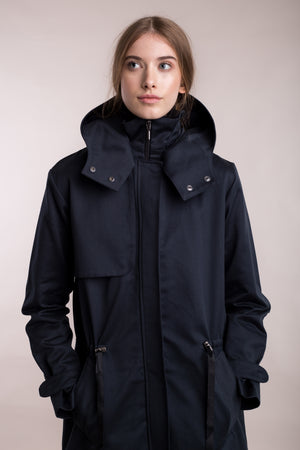 The model wears a dark blue sustainable organic cotton hooded water-resistant coat.