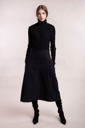 The model wears a black midi-lenght sustainable organic cotton A-line skirt, frontal view.