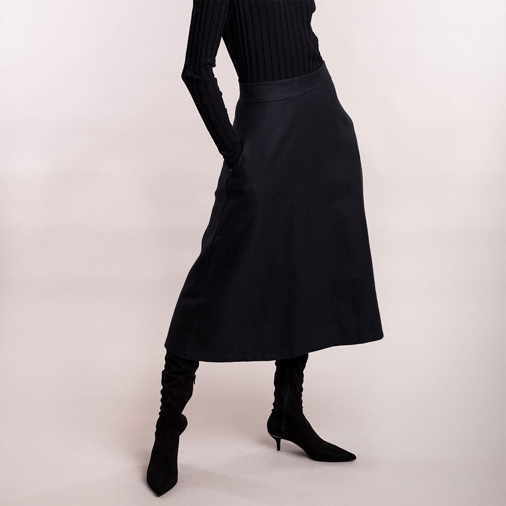 The model wears a black midi-lenght sustainable organic cotton A-line skirt, close up view.