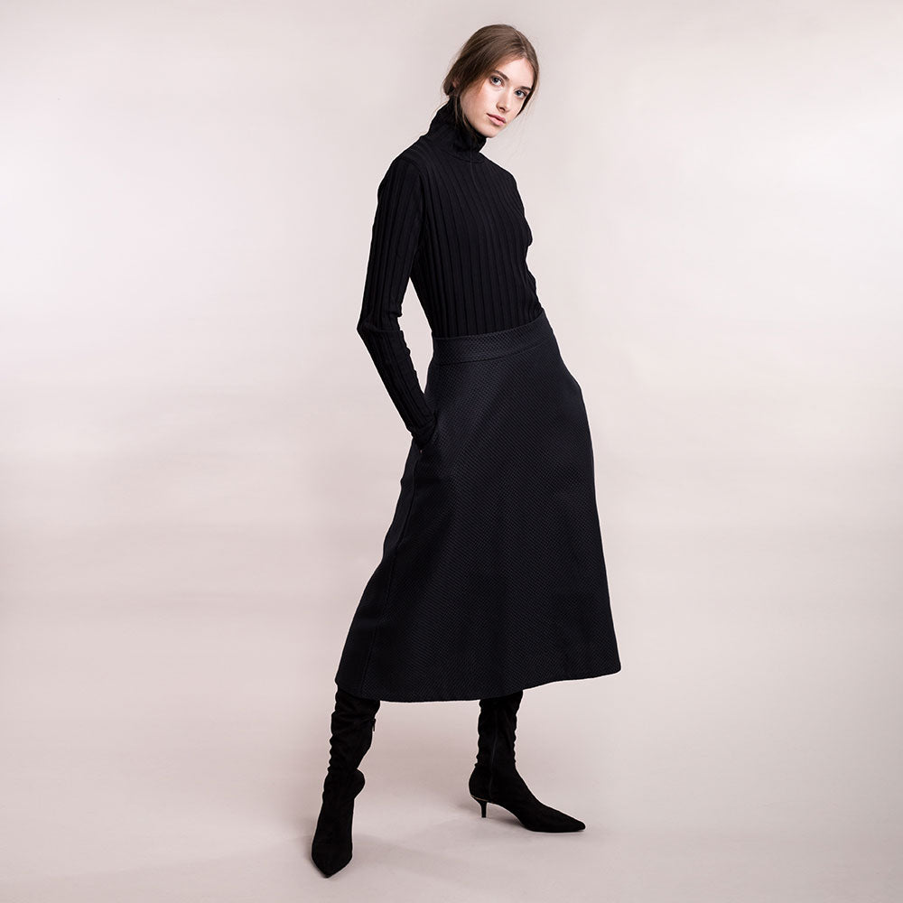 The model wears a black midi-lenght sustainable organic cotton A-line skirt, frontal side view.