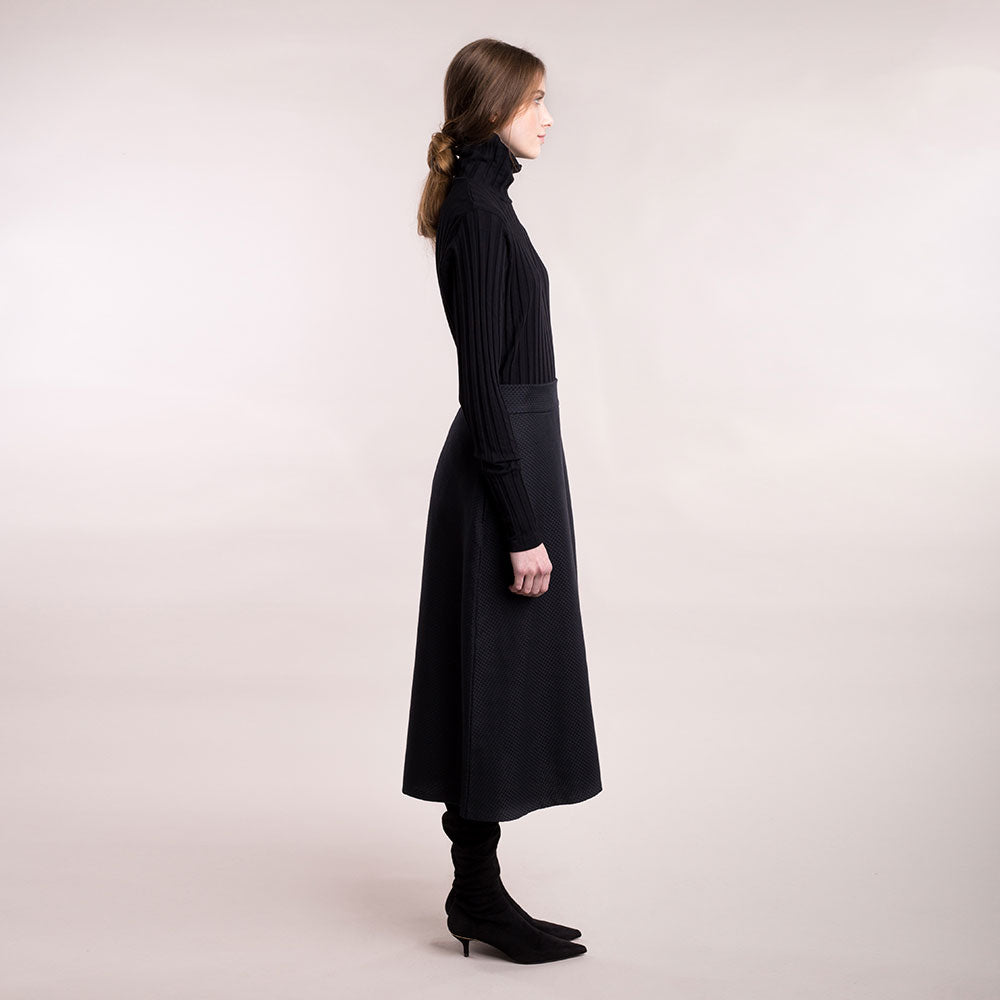 The model wears a black midi-lenght sustainable organic cotton A-line skirt, side view.