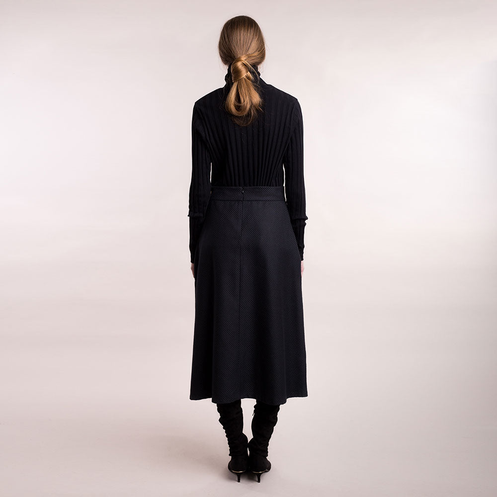 The model wears a black midi-lenght sustainable organic cotton A-line skirt, back view.