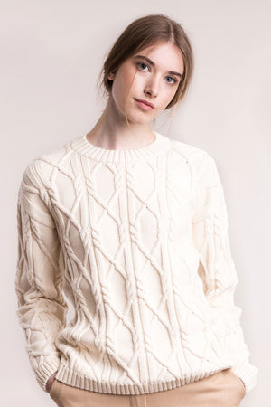 The model wears a cream sustainable organic cotton knitted aran pullover, frontal view.