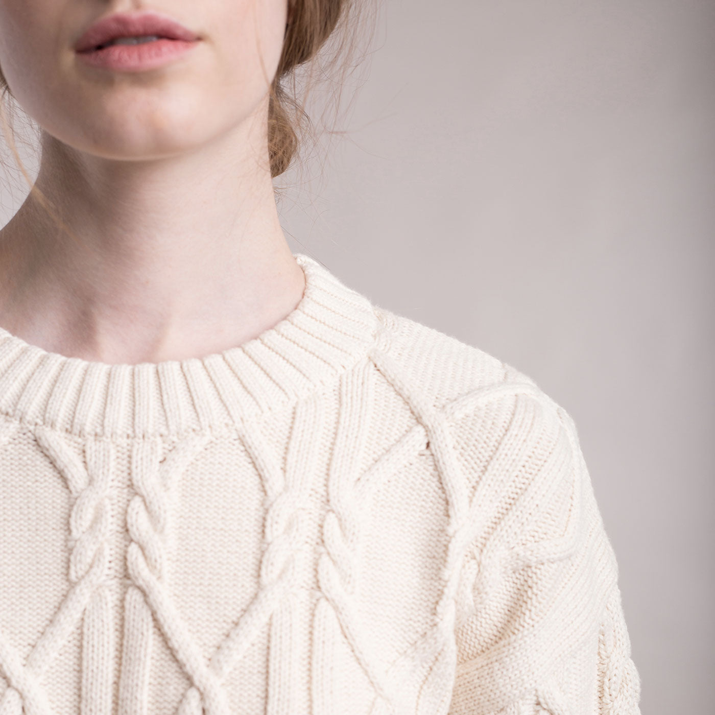 The model wears a cream sustainable organic cotton knitted aran pullover, detail low neck.
